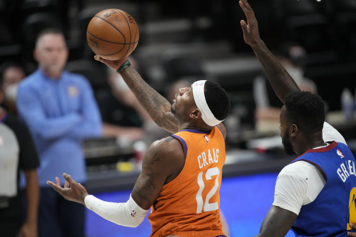 Phoenix Suns forward Torrey Craig, left, drives to the basket past Denver Nuggets forward JaMychal Green during the first half of Game 3 of an NBA second-round playoff series Friday, June 11, 2021, in Denver. (AP Photo/David Zalubowski)