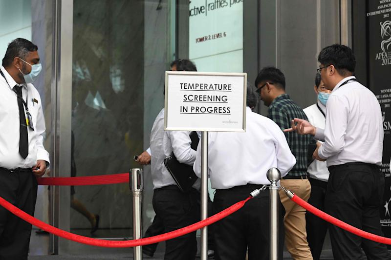 """Building management staff conduct temperature screenings of visitors and tenants of a building in the financial district of Singapore on February 10, 2020, in the wake of the spread of the novel coronavirus. - Singapore, which has reported 33 cases of people infected with novel coronavirus, raised its alert level on February 7 to """"orange"""" -- the same as during the deadly 2003 SARS outbreak, indicating the virus is severe and passes easily between people. (Photo by Roslan RAHMAN / AFP) (Photo by ROSLAN RAHMAN/AFP via Getty Images)"""