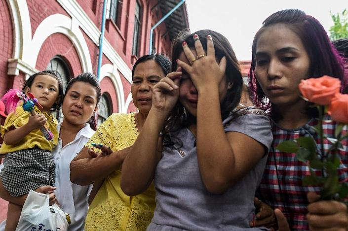 Kyaw Soe Oo's wife Chit Su Win(2nd-R) grieves with family after the verdict is revealed (AFP Photo/Ye Aung THU)