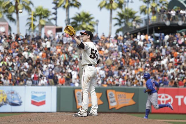 San Francisco Giants starting pitcher Tim Lincecum, center, stands on the mound after giving up a home run to the Chicago Cubs' Welington Castillo, right, who circles the bases in the seventh inning of their baseball game on Sunday, July 28, 2013, in San Francisco. (AP Photo/Eric Risberg)