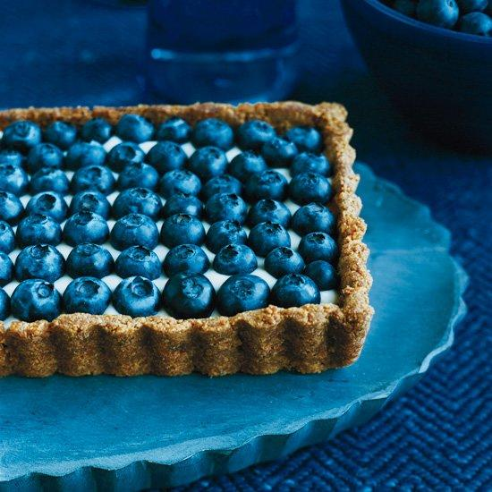 """<p>Melissa Rubel mixes creamy yogurt with honey so it's deliciously sweet and tangy, then she spreads it in a graham-cracker crust spiced with bits of crystallized ginger and tops it with plump blueberries.</p><p><a href=""""https://www.foodandwine.com/recipes/honeyed-yogurt-and-blueberry-tart-with-ginger-crust"""">GO TO RECIPE</a></p>"""