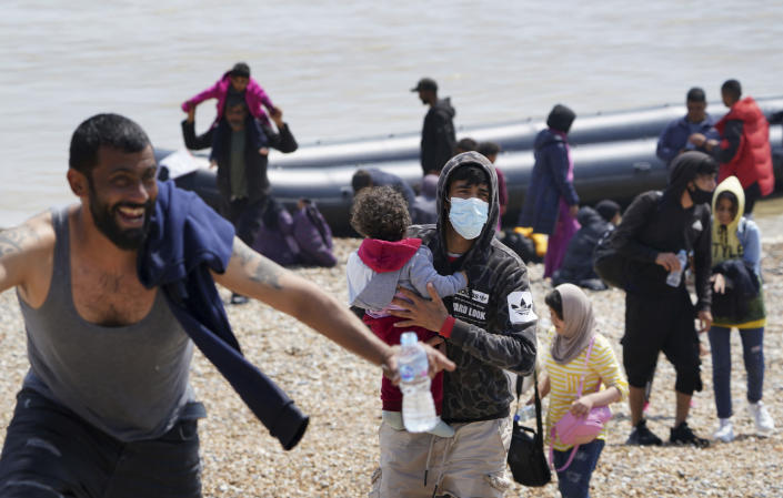 People thought to be migrants make their way up the beach after arriving on a small boat at Dungeness in Kent, England, Monday, July 19, 2021. They were later taken away by Border Force staff. (Gareth Fuller/PA via AP)