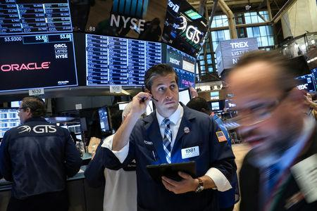 FILE PHOTO: Traders work on the floor at the New York Stock Exchange (NYSE) in New York, U.S., April 8, 2019. REUTERS/Brendan McDermid