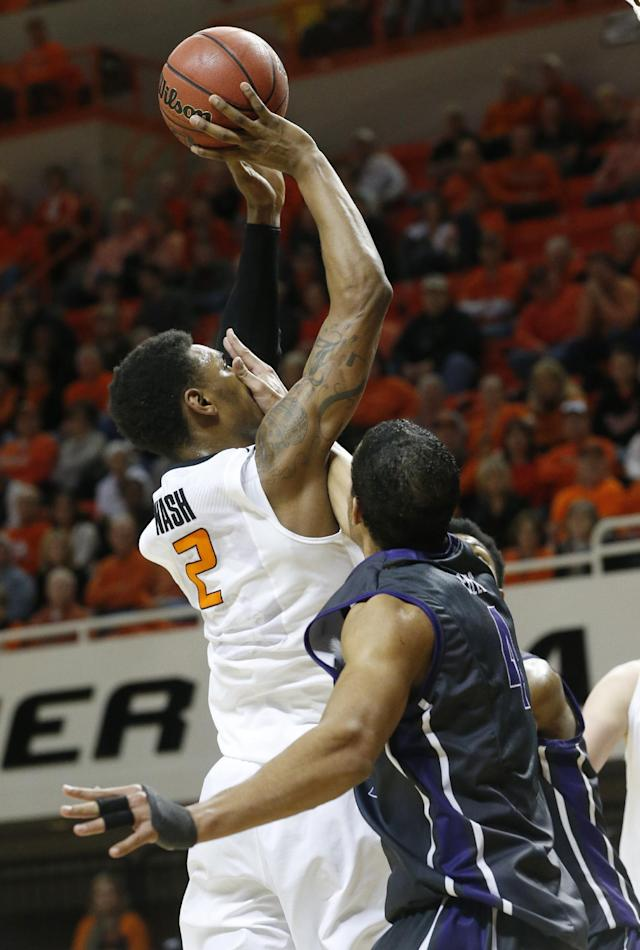 Oklahoma State wing Le'Bryan Nash (2) is fouled by TCU forward Amric Fields (4) as he shoots during the second half of an NCAA college basketball game in Stillwater, Okla., Wednesday, Jan. 15, 2014. Oklahoma State won 82-50. (AP Photo/Sue Ogrocki)