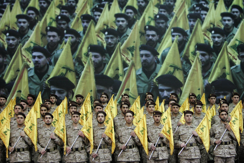 FILE - In this February 22, 2008 file photo, Hezbollah fighters hold their party flags as they attend a rally to commemorate slain top Hezbollah commander Imad Mughniyeh and two other leaders, Abbas Musawi and Ragheb Harb, in the Shiite suburb of Beirut, Lebanon. Lebanon's prime minister has expressed his readiness to cooperate with Bulgarian authorities over a bomb attack linked to Hezbollah that killed five Israelis and their Bulgarian driver, in a statement Tuesday, Feb. 5, 2013. Prime Minister Najib Mikati whose Cabinet is dominated by members of the Shiite Muslim group and its allies also says he condemns and rejects any attack that targets an Arab or foreign country.(AP Photo/Hussein Malla, File)