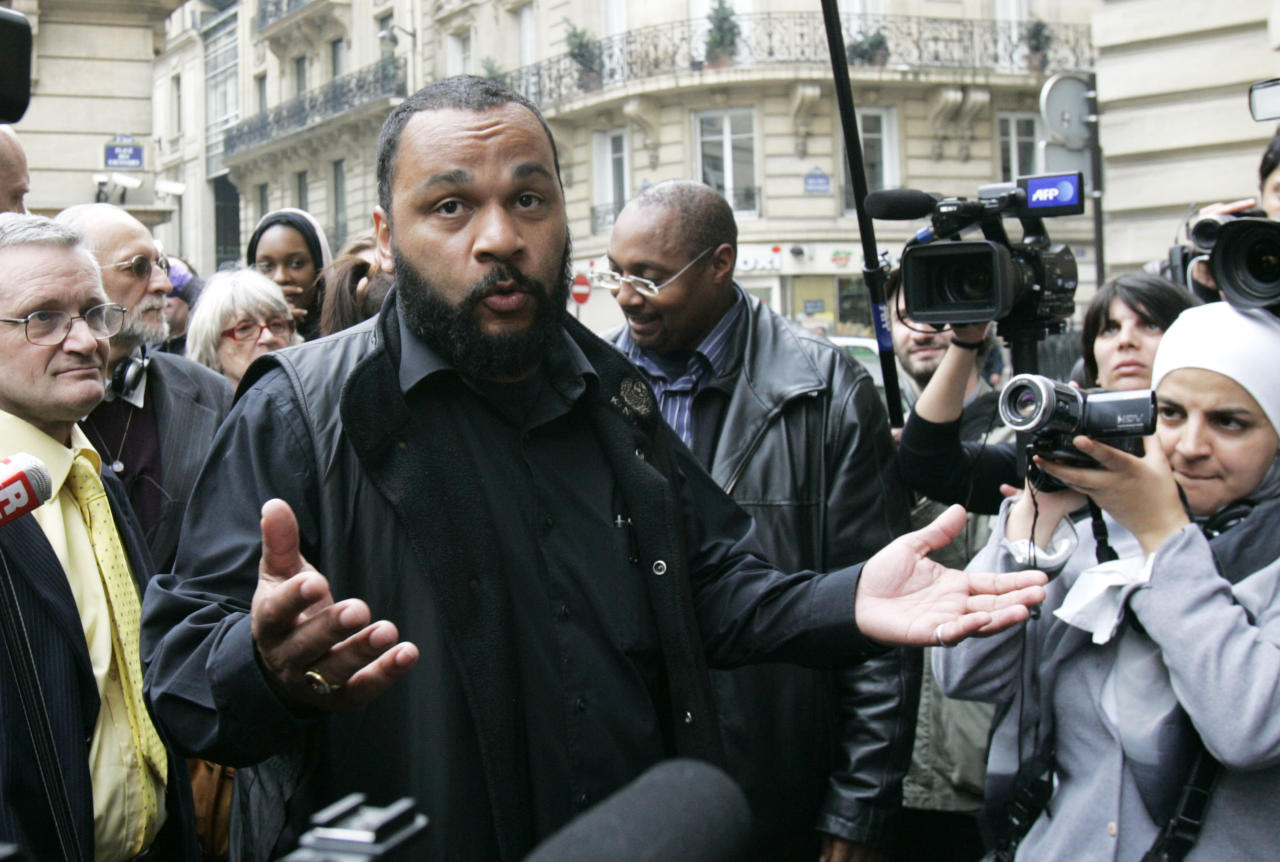 FILE - In this May 13, 2009 file photo, controversial French comic Dieudonne M'Bala M'Bala, known as Dieudonne, answers reporters as he heads for the interior Ministry to submit a list of candidates for the upcoming European elections, in Paris. The Paris prosecutor's office said Thursday Jan. 2, 2013, it is investigating threats against a comedian the French interior minister wants banned from the stage for what he says are racist and anti-Semitic performances. (AP Photo/Remy de la Mauviniere, File)