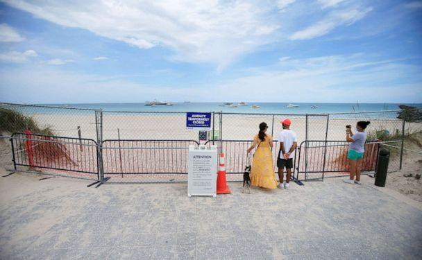 PHOTO: People look through fencing next to signage indicating that the beach is temporarily closed in South Pointe park, July 4, 2020, in the South Beach neighborhood of Miami Beach, Fla. (Cliff Hawkins/Getty Images)