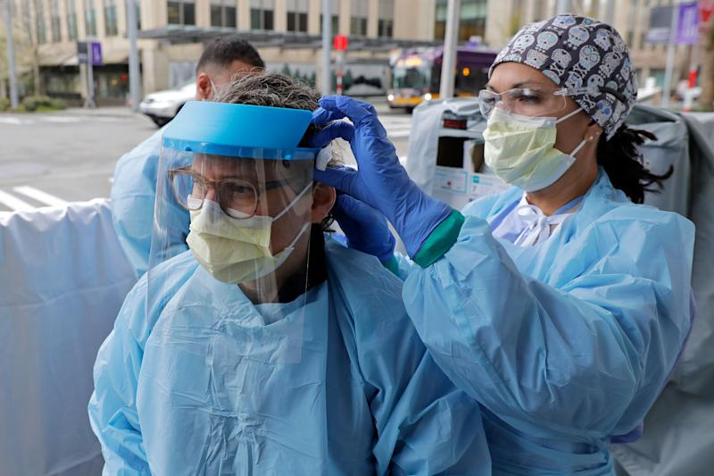 An emergency services nurse at Harborview Medical Center in Seattle helps a colleague put on a medical face shield prior to their shift in a triage tent used for arriving patients who have respiratory symptoms. (Photo: ASSOCIATED PRESS)