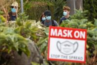 People wear masks as they walk along the side walk during the outbreak of the coronavirus disease in California