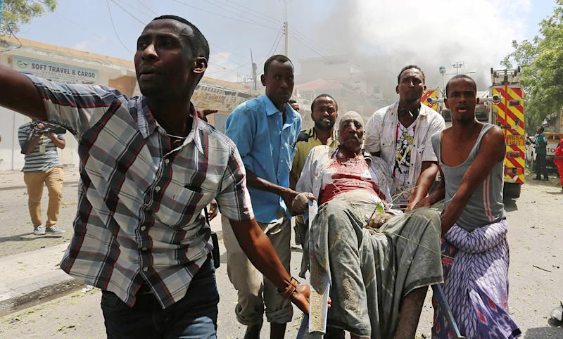 <p>Rescuers carry an injured man from the scene of an explosion near Wehliye Hotel on Maka al Mukaram street in Somalia's capital Mogadishu, March 13, 2017. (Feisal Omar/Reuters) </p>