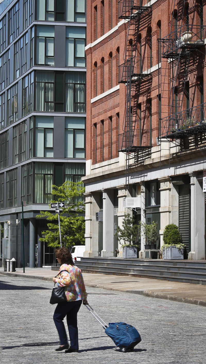 A modern luxury glass apartment building, left, sits across the street from an older red brick apartment, the home of photographer Arne Svenson, Thursday, May 16, 2013 in New York. Residents of a New York luxury apartment building are livid over an exhibition of photos secretly snapped through their apartment windows. (AP Photo/Bebeto Matthews)