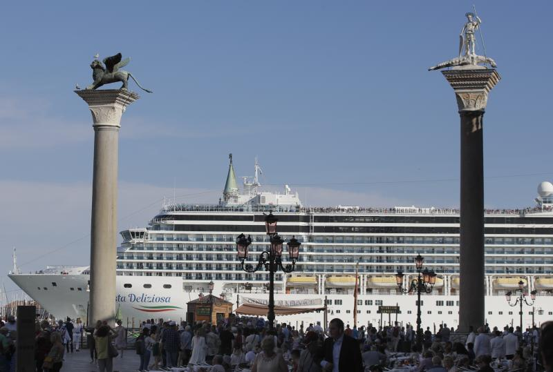 A cruise ship passes by St. Mark's Square in Venice, Italy, Sunday, June 2, 2019. Groups that want to ban cruise ships on Venice's busy canals say a collision that injured four tourists has served as a wake-up call. Opponents say cruise ships are out-of-scale for Venice, cause pollution, threaten the lagoon's ecosystem and dangerous. (AP Photo/Luca Bruno)