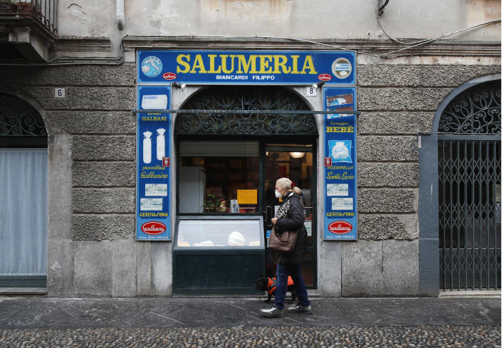 In this photo taken on Thursday, March 12, 2020, a woman walks past a deli meat and cold cuts shop in Codogno, Italy. The northern Italian town that recorded Italy's first coronavirus infection has offered a virtuous example to fellow Italians, now facing an unprecedented nationwide lockdown, that by staying home, trends can reverse. Infections of the new virus have not stopped in Codogno, which still has registered the most of any of the 10 Lombardy towns Italy's original red zone, but they have slowed. For most people, the new coronavirus causes only mild or moderate symptoms. For some it can cause more severe illness. (AP Photo/Antonio Calanni)