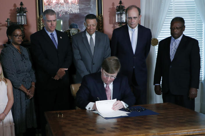 Mississippi Republican Gov. Tate Reeves signs the bill retiring the last state flag in the United States with the Confederate battle emblem, at the Governor's Mansion in Jackson, Miss., Tuesday, June 30, 2020. Standing behind Reeves are, from left, Sen. Angela Turner Ford, D-West Point; House Speaker Philip Gunn, R-Clinton; Reuben Anderson, former Mississippi Supreme Court Justice; Lt. Gov. Delbert Hosemann; and Transportation Commissioner for the Central District Willie Simmons. After Reeves signed the bill, the flag lost its official status. (AP Photo/Rogelio V. Solis, Pool)