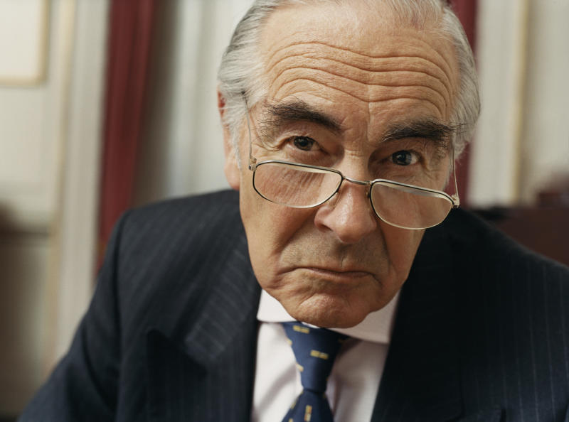 A visibly irritated senior man in a suit with a scowl on his face.