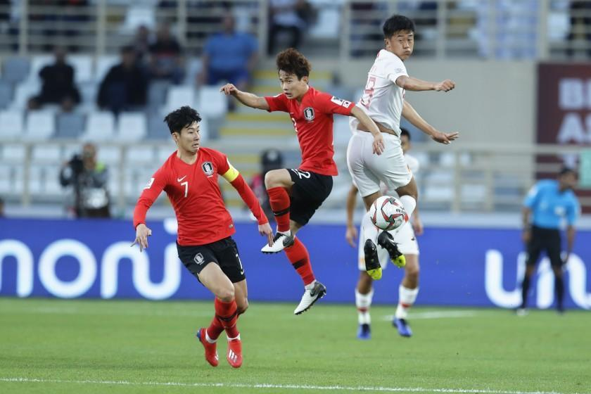 China's defender Liu Yang and South Korea's defender Kim Moon-Hwan jump for the ball during the AFC Asian Cup group C soccer match between South Korea and China at Al Nahyan Stadium in Abu Dhabi, United Arab Emirates, Wednesday, Jan. 16, 2019. (AP Photo/Hassan Ammar)