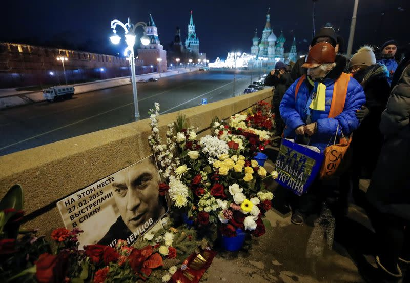 An elderly woman visits the site of the assassination of politician Boris Nemtsov while marking the fourth anniversary of Nemtsov's death in central Moscow