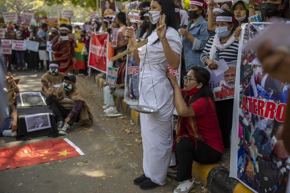 A Chin refugee from Myanmar adjusts the dress of another refugee dressed as lady justice during a protest against military coup in Myanmar, in New Delhi, India, Wednesday, March 3, 2021. (AP Photo/Altaf Qadri)