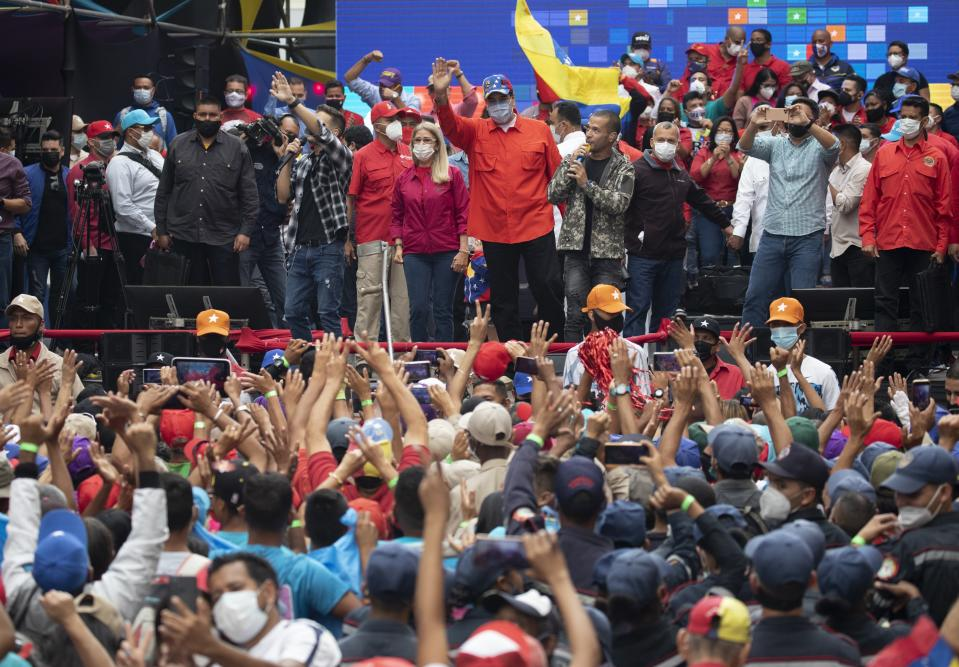 Venezuela's President Nicolas Maduro, center, and first lady Cilia Flores who is also a candidate for the National Assembly, wave at supporters during a closing campaign rally for the upcoming National Assembly elections in Caracas, Venezuela, Thursday, Dec. 3, 2020. Venezuelans will vote for a new National Assembly this Sunday, Dec 6. (AP Photo/Ariana Cubillos)