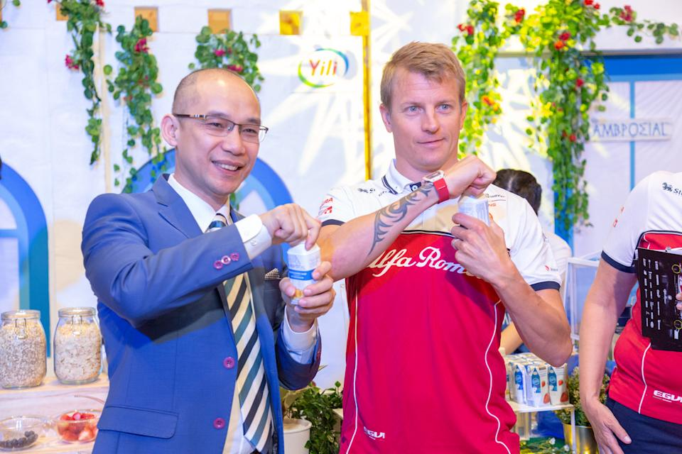 Alfa Romeo Racing driver Kimi Raikkonen (right) at the launch event of Ambrosial yoghurt at Marina Bay Sands, together with Leslie Huang, Yili Group's general manager of international business. (PHOTO: Ricky Ee/Ambrosial)