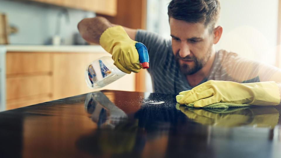 Shot of a young man cleaning the kitchen counter at home.