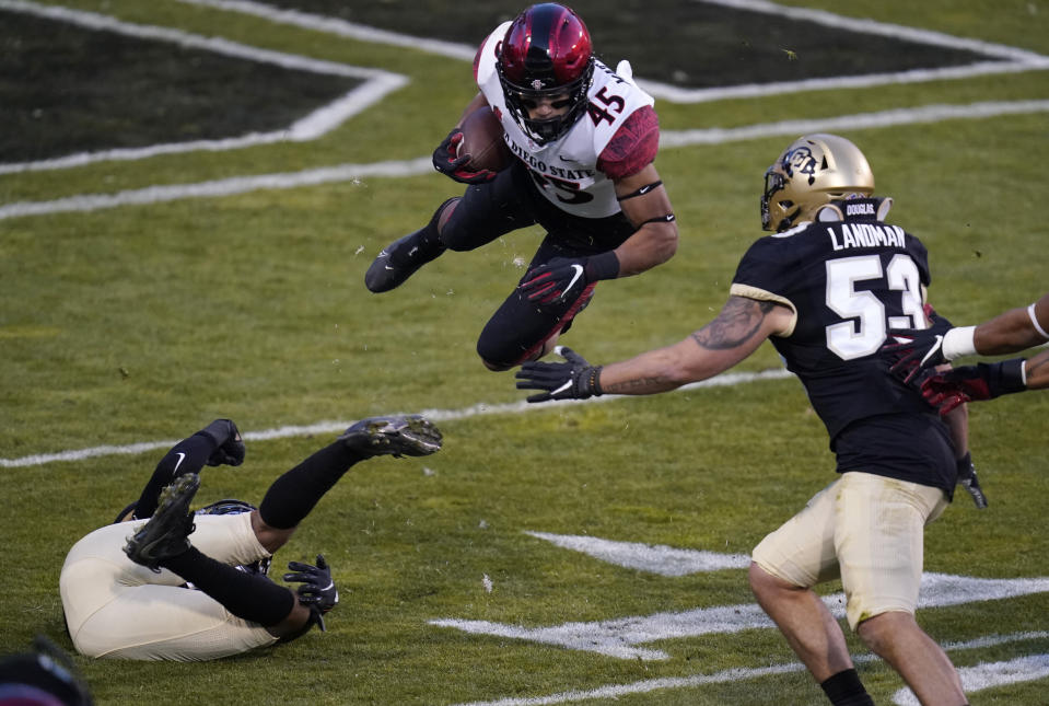 San Diego State wide receiver Jesse Matthews, center, flies after being hit by Colorado safety Derrion Rakestraw, left, as Colorado linebacker Nate Landman comes in for the stop in the first half of an NCAA college football game Saturday, Nov. 28, 2020, in Boulder, Colo. (AP Photo/David Zalubowski)