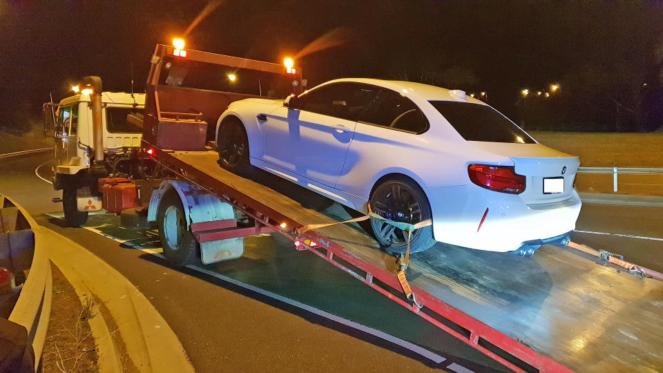 A white BMW M2 is confiscated by police at Bowen Bridge, Tasmania.