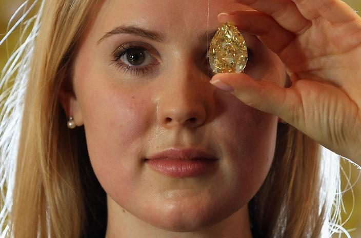 LONDON, ENGLAND - OCTOBER 24: A Sotheby's employee holds a 110.03 carat sun-drop diamond on October 24, 2011 in London, England. The diamond is the largest yellow pear-shaped diamond in the world. (Photo by Dan Kitwood/Getty Images)