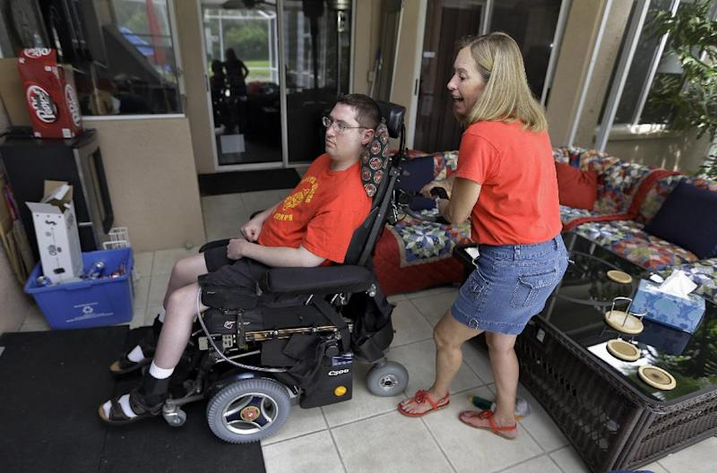 Chris Ott, right, helps her son, former Marine John Thomas Doody. J.T., who was shot while serving in Fallujah, Iraq., subsequently suffering an infection and a series of strokes that left him in a coma and relying on a ventilator to survive, Tuesday, Sept. 3, 2103, in Riverview, Fla. The Department of Veterans Affairs said Wednesday it supports expanding an enhanced caregivers benefit for grievously wounded veterans but only if Congress comes up with the billions needed to fund it. Congress created the program in 2010, giving caregivers of seriously wounded veterans a stipend, health care and at least 30 days of respite care each year. But it was limited to veterans who served after the Sept. 11 terrorist attacks. Lawmakers told the VA to study the feasibility of expansion after some veterans groups raised questions about fairness. (AP Photo/Chris O'Meara)