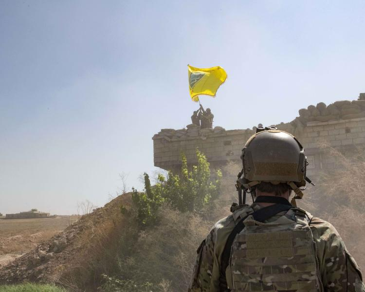 """In this Sept. 21, 2019, photo, released by the U.S. Army, a U.S. soldier oversees members of the Syrian Democratic Forces as they demolish a Kurdish fighters' fortification and raise a Tal Abyad Military Council flag over the outpost as part of the so-called """"safe zone"""" near the Turkish border. (U.S. Army photo by Staff Sgt. Andrew Goedl via AP)"""
