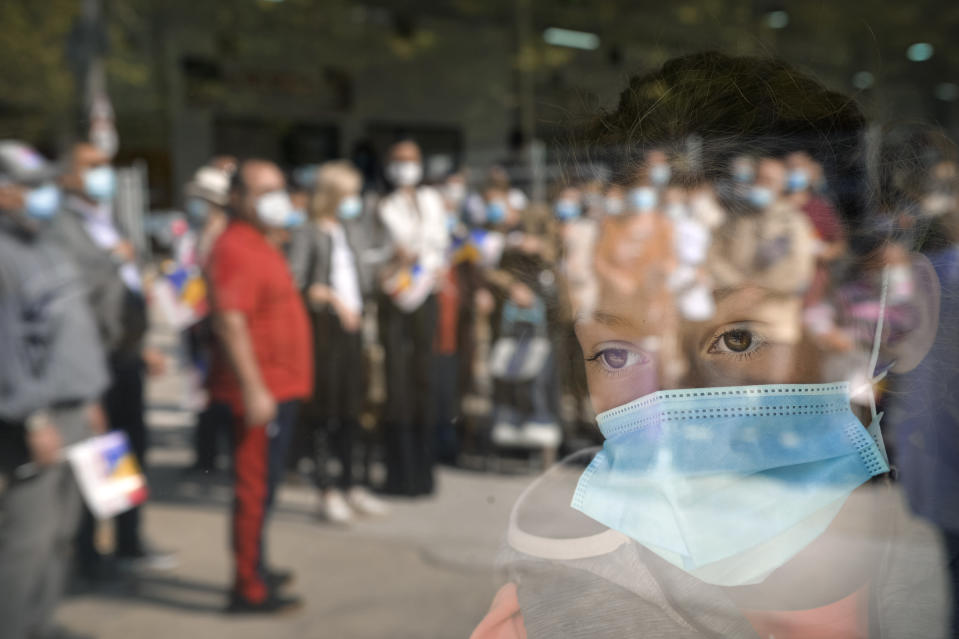 FILE - In this Sept. 19, 2020 file photo, a young girl wearing a mask for protection against COVID-19 infection watches people waiting for the opening of a market selling Romanian food products in Bucharest, Romania. Romania registered on Wednesday, Oct. 7, 2020, the highest levels of COVID-19 infections in 24 hours since the pandemic reached the county in February, with 2958 new cases, the highest number of fatalities, 82 and people in ICU units 612. (AP Photo/Andreea Alexandru, File)