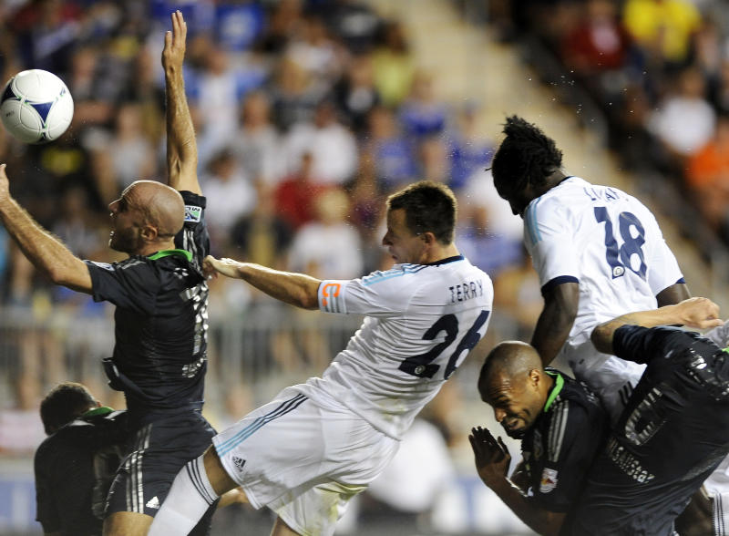 Chelsea FC's John Terry (26) heads the ball over MLS All-Stars' Aurelien Collin (78), of Sporting Kansas City, to score during the first half of soccer's MLS All-Star game, Wednesday, July 25, 2012, in Chester, Pa. (AP Photo/Michael Perez)