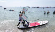 Paddleboarders and surfers take part in a paddle out to raise awareness for climate action in the sea at Gyllyngvase Beach in Falmouth, Cornwall, England, Saturday, June 12, 2021. Leaders of the G7 gather for a second day of meetings on Saturday, in which they will discuss COVID-19, climate, foreign policy and the economy. (AP Photo/Alastair Grant)