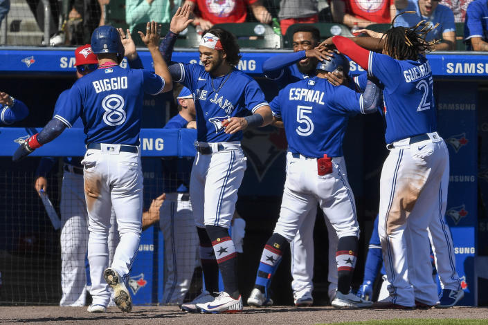 Toronto Blue Jays' Santiago Espinal (5) and Cavan Biggio (8) are congratulated by teammates after scoring on Espinal's two-run home run against the Tampa Bay Rays during the sixth inning of a baseball game in Buffalo, N.Y., Saturday, July 3, 2021. (AP Photo/Adrian Kraus)
