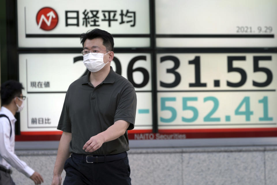 A man wearing a protective mask walks in front of an electronic stock board showing Japan's Nikkei 225 index at a securities firm Wednesday, Sept. 29, 2021, in Tokyo. Asian shares fell sharply on Wednesday after a broad slide on Wall Street as investors reacted to a surge in U.S. government bond yields. (AP Photo/Eugene Hoshiko)