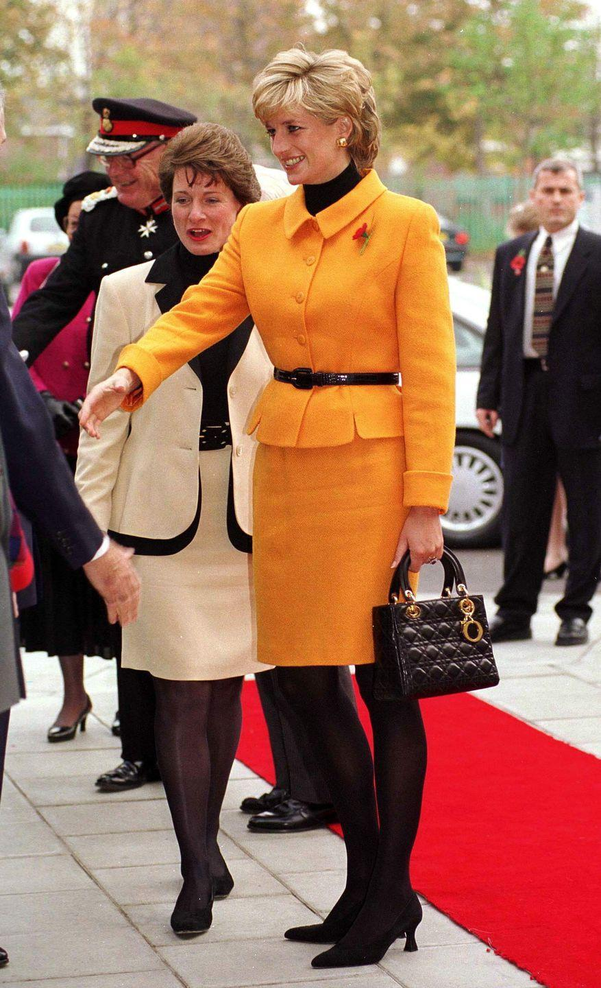 <p>In a bright orange suit by Versace and a handbag by Christian Dior at an event in Liverpool, England. </p>