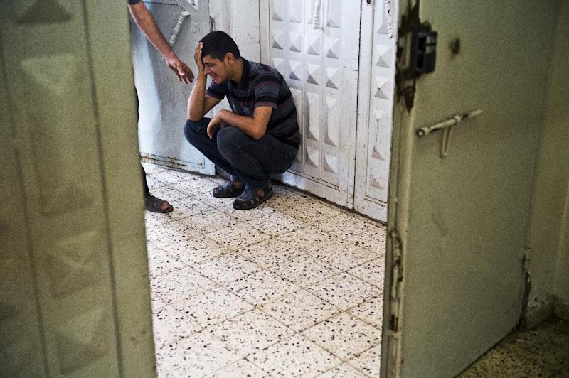 A Palestinian man grieves against in morgue after seeing the body of his relative who was killed in an Israeli airstrike in Gaza City on August 24, 2014