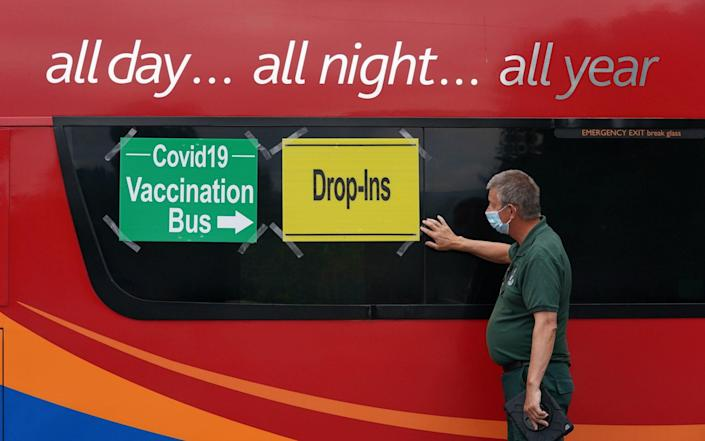 In Scotland, paramedic Dougie Blues puts signs on a vaccination bus in the car park of Crieff Community Hospital - Andrew Milligan/ PA