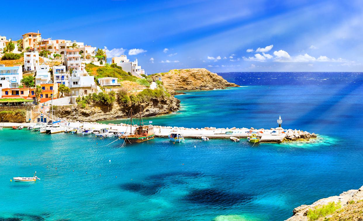 Harbour with marine vessels, boats and lighthouse. Panoramic view from a cliff on a Bay with a beach and architecture Bali - vacation destination resort, with secluded beaches and clear turquoise ocean waters, Rethymno, Crete, Greece