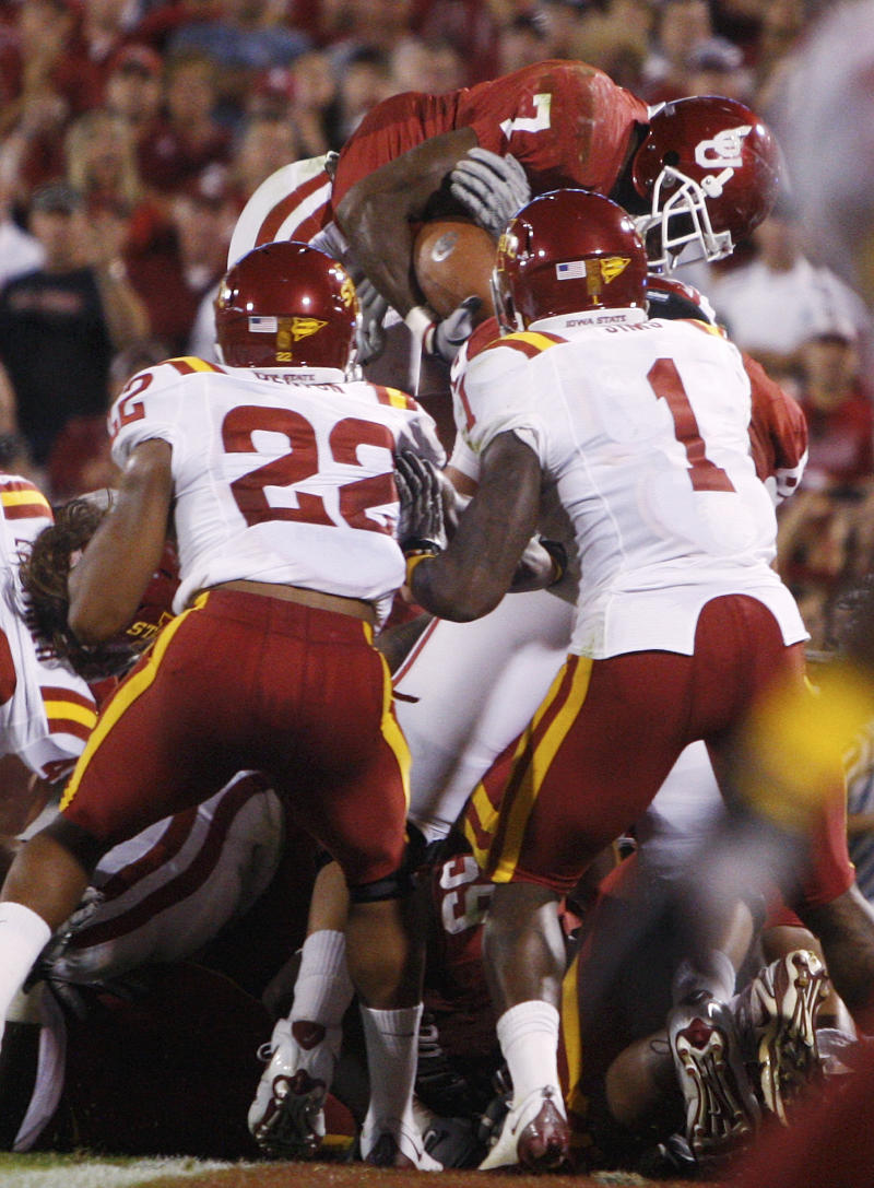 Oklahoma running back DeMarco Murray, top goes up and over the Iowa State defensive line for a touchdown in the second quarter of an NCAA college football game in Norman, Okla., Saturday, Oct. 16, 2010. Iowa State defensive back Ter'Ran Benton, left, and defensive back David Sims, right, look on. (AP Photo/Sue Ogrocki)