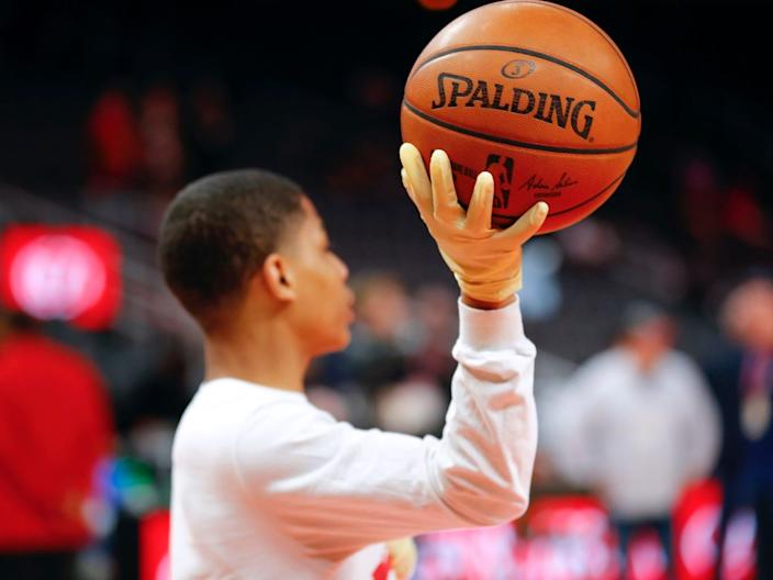 A ball boy wears gloves while handling a ball during warm-ups.