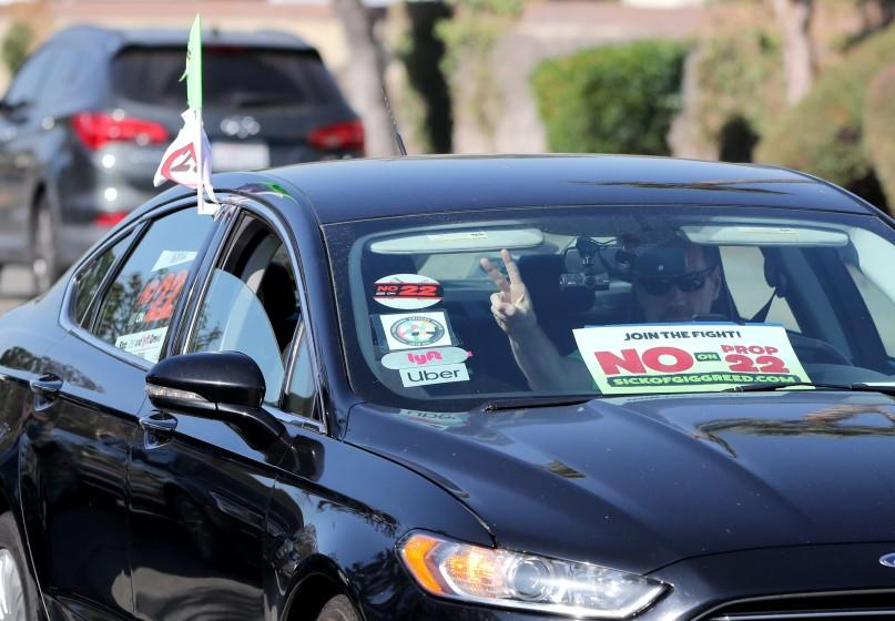 A vehicle with Uber and Lyft stickers arrive at press conference about voting no on proposition 22, in solidarity with Uber and Lyft drivers, at the IBEW headquarters in the city of Orange on Friday, Oct. 16, 2020.