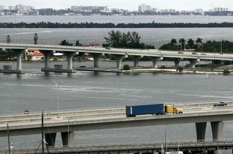 A truck transports a container into a port of Miami