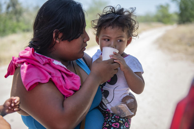 An illegal immigrant gives her daughter water