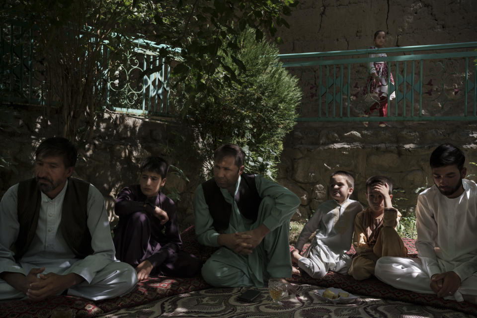 Painda Mohammed, left, sits with family members at their house's yard near Kabul, Afghanistan, Friday, Sept. 17, 2021. Painda's son, Fida Mohammad died after falling from a departing U.S. Air Force C-17 taking off from Kabul's International Airport. (AP Photo/Felipe Dana)