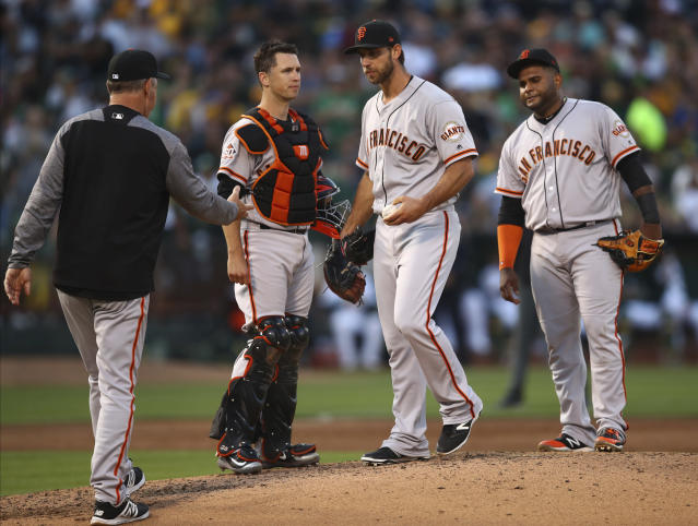 San Francisco Giants manager Bruce Bochy, left, relieves pitcher Madison Bumgarner, second from right, in the fifth inning of a baseball game against the Oakland Athletics, Saturday, July 21, 2018, in Oakland, Calif. (AP Photo/Ben Margot)