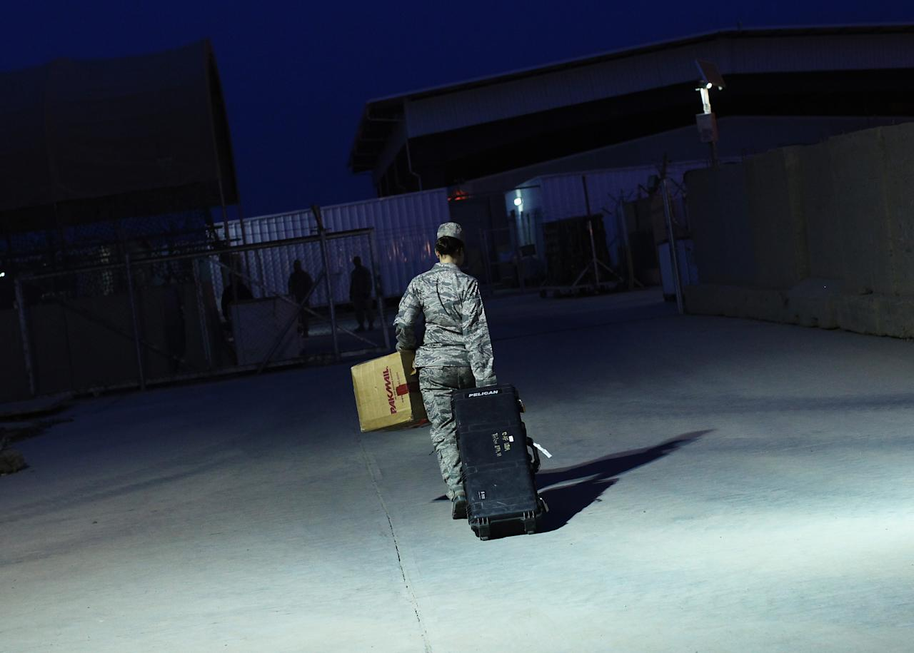 U.S. Air Force Major Stacie Shafran carries her luggage to a loading paddock while waiting for her departure from Iraq at the former U.S. Sather Air Base near Baghdad, Iraq December 14, 2011. The former base that is currently still operational was handed over to the Baghdad Diplomatic Support Center run by the State Department on December 1st.  REUTERS/Shannon Stapleton  (IRAQ - Tags: MILITARY CONFLICT SOCIETY)