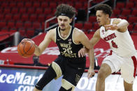 Wake Forest's Ismael Massoud (25) drives by North Carolina State's Jericole Hellems (4) during the first half of an NCAA college basketball game Wednesday, Jan. 27, 2021, in Raleigh, N.C. (Ethan Hyman/The News & Observer via AP, Pool)