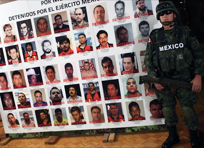 "An army soldier stands next to a banner displaying mug shots of persons detained or killed by the Mexican Army during the media presentation of Daniel Ramirez, alias ""El Loco"", not pictured, in Mexico City, Monday, May 21, 2012. Ramirez is believed to be a member of the Zetas drug cartel allegedly involved in the dumping of more than 40 hacked-up bodies on a highway outside the city of Cadereyta near Monterrey. The bodies with their heads, hands and feet hacked off were found May 13. (AP Photo/Alexandre Meneghini)"