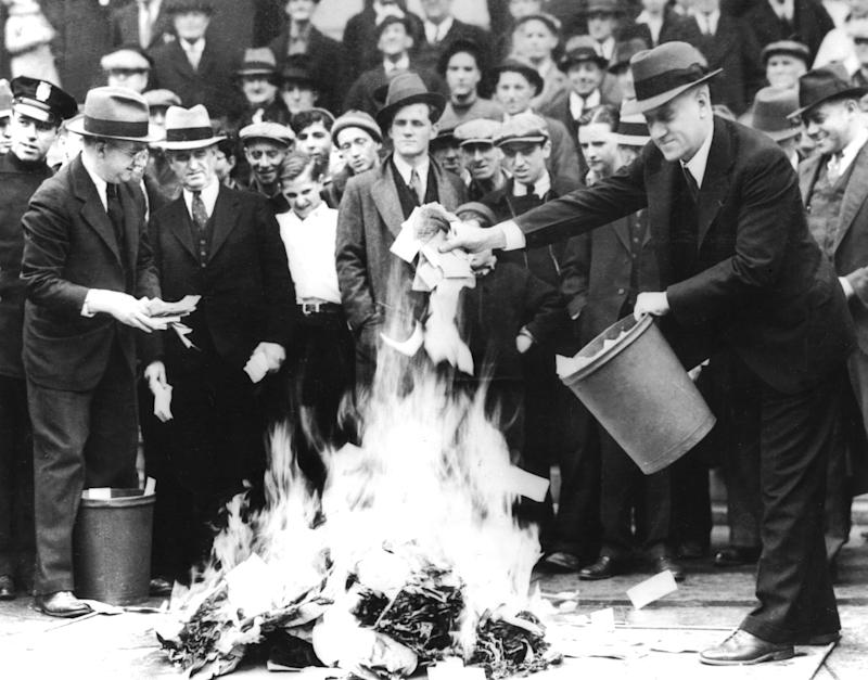 """City council man, Mr. Barlow, and Treasury Secretary, Mr. Jil Martin, burning 100,000 dollars of """"scrip money"""" (after the banks' closure),, April 1933,, United States,, National archives. Washington. (Photo by: Photo12/Universal Images Group via Getty Images)"""